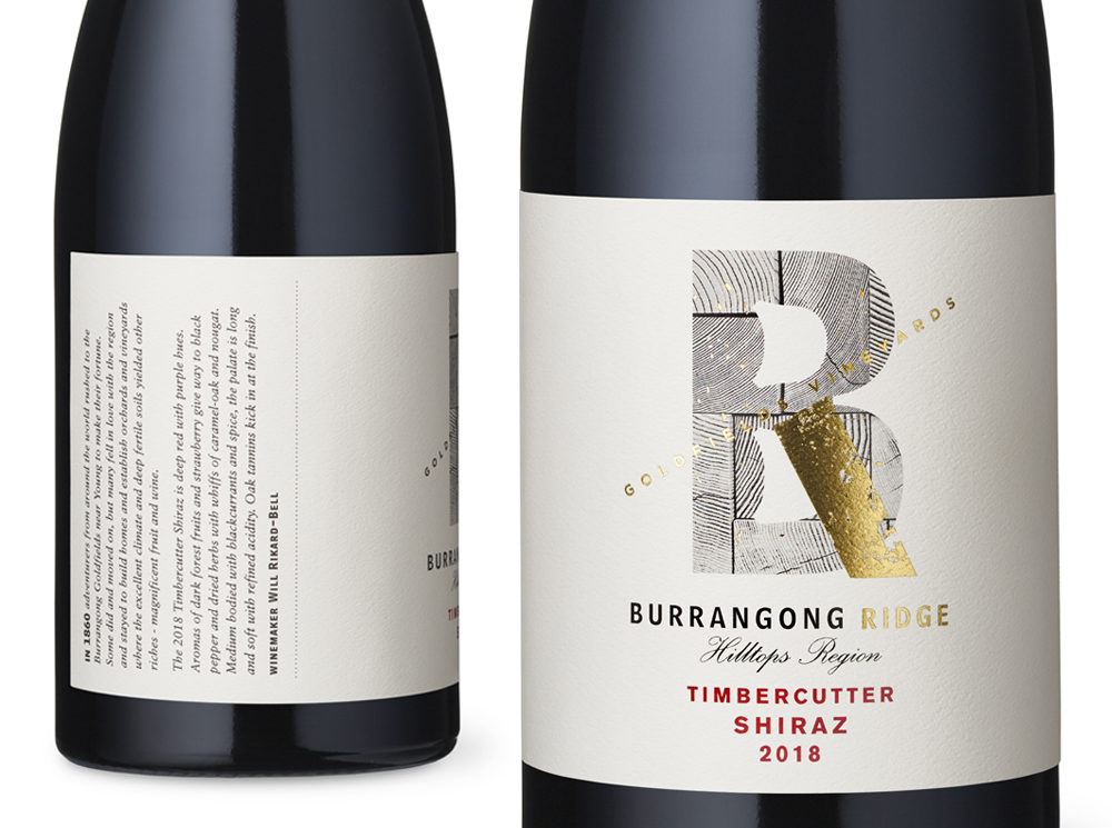 The label design combines the B and the R of the brand name with a streak / flecks of gold. The textured timber background relates to the product name Timbercutter Shiraz